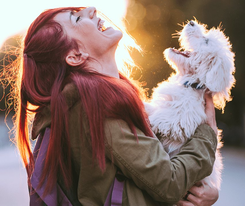woman holding small howling dog